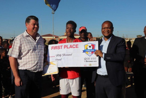 H.T.S Louis Botha Team Captain Luvuyo Sekoena (Grade 12), with the school principal, Mr Charles Liversage and MEC Tate Makgoe. Louis Botha won the Lemo Mall Cup Football Tournament, for the three years in a row since its inception in 2017.